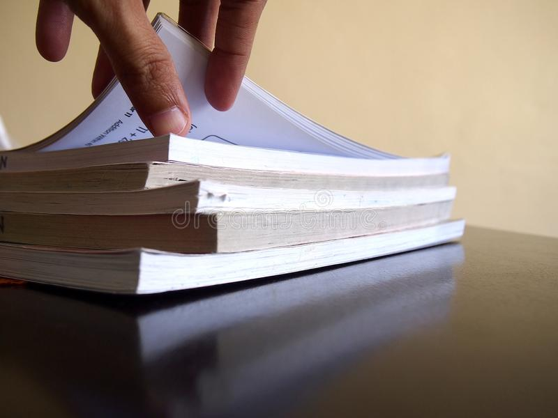 Stapel von Büchern und eine Hand, die eine Seite öffnet stockfotos
