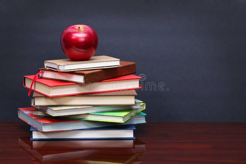 Stapel von Büchern und von rotem Apfel auf dem Schreibtisch über der Tafel lizenzfreies stockfoto
