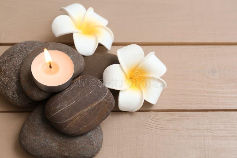 Stapel von Badekurortsteinen mit brennender Kerze und Blumen auf hölzernem Hintergrund stockfoto