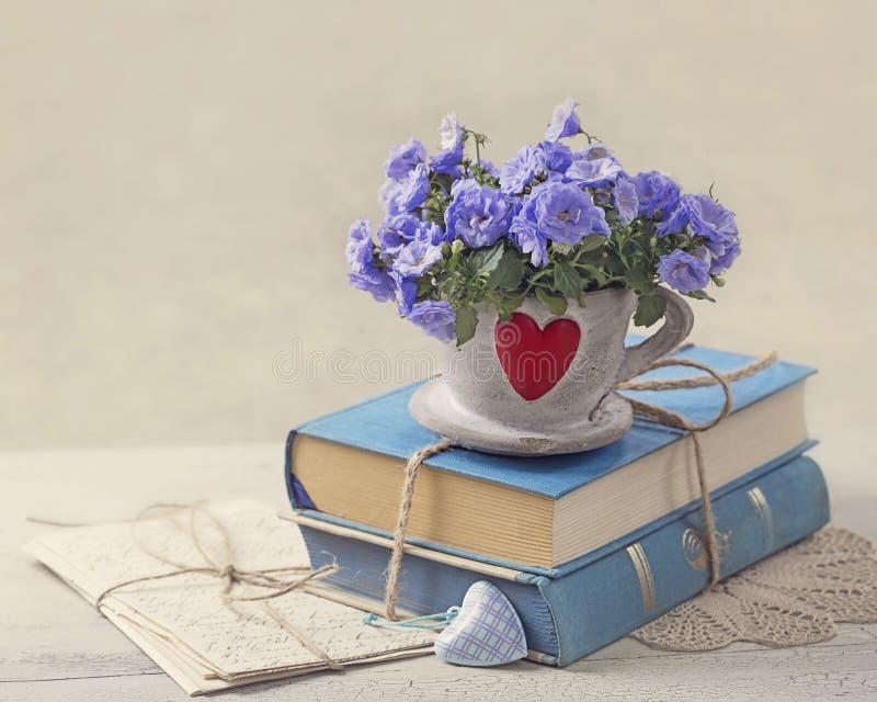 Stapel von blauen Büchern und von Blumen stockfoto