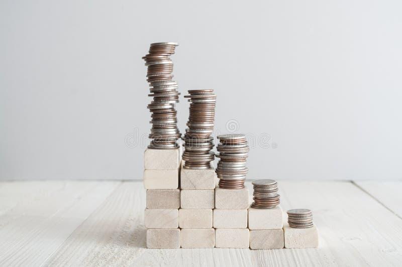 Stapel von den Münzen, die auf hölzerner Treppe stehen stockfoto