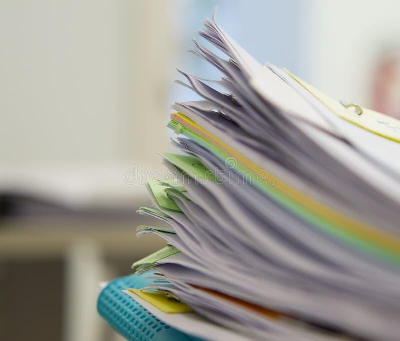 Stapel von Dokumenten und von blauer Datei im Bürohintergrund lizenzfreie stockbilder