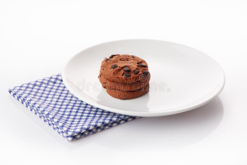 Stapel von drei selbst gemachten Schokoladensplitterplätzchen auf weißer keramischer Platte auf blauer Serviette lizenzfreie stockfotos