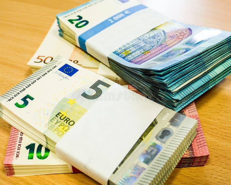Stapel von eingewickelten Eurorechnungen auf einem Kiefernschreibtisch stockbilder