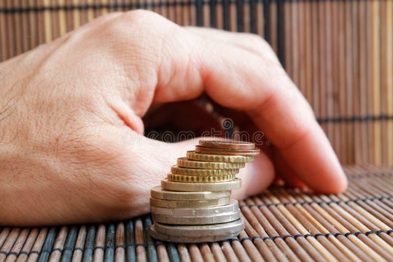 Stapel von Euromünzen, wie einem Turm liegt auf hölzerner Bambustabelle, Mann ` s Hand auf Hintergrund stockbild