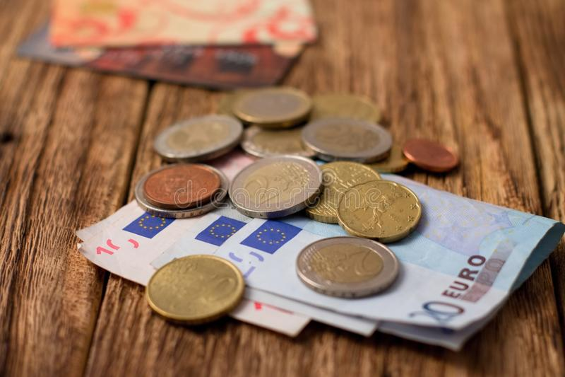 Stapel von Eurorechnungen und von Münzen plus zwei Kreditkarten lizenzfreie stockfotos