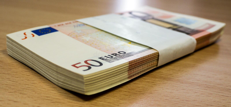 Stapel von fünfzig Eurorechnungen auf einem Kiefernschreibtisch stockbild