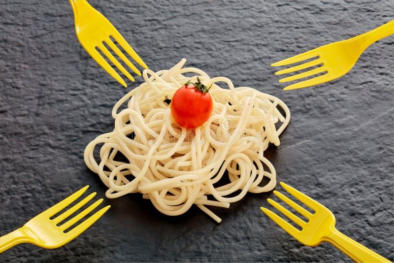 Stapel von gekochten Teigwarenspaghettis, von Kirschtomate und von Gabeln stockfotografie