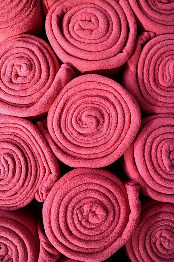 Stapel von gerollt herauf vibrierendes Rosa färbte Vlies-Decken, vertikales Foto für Hintergrund lizenzfreie stockfotos