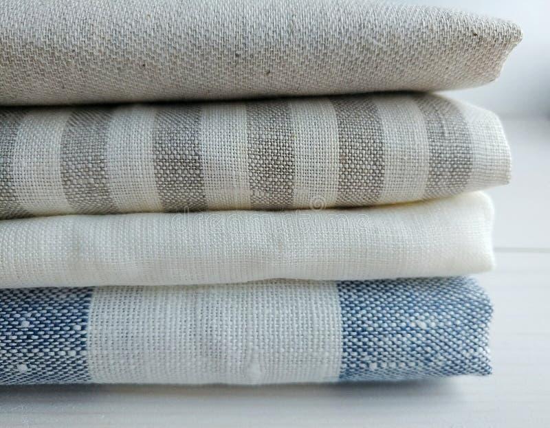 Stapel von gestreiften weißen grauen blauen Leinenbaumwollgewebe auf weißem Hintergrund stockfoto