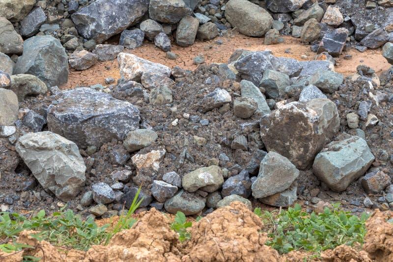 Stapel von großen Granitsteinen nahe dem Gras lizenzfreie stockfotos