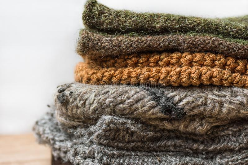 Stapel von handgemachtem wärmen gestrickte Socken-Schal-Handschuhe von rauem beige Grau Wollgarn-Browns auf hölzerner Tabelle Abs lizenzfreies stockfoto