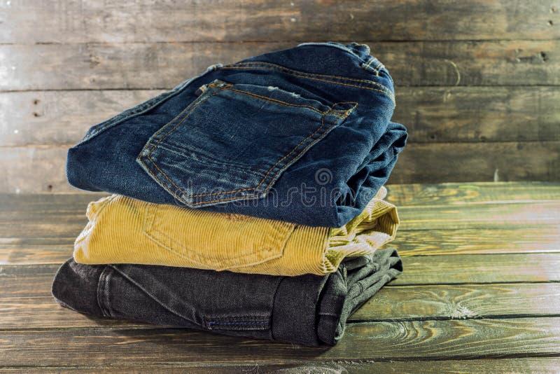Stapel von Hosen von den verschiedenen Farben braun, blau und schwarz auf einem hölzernen Regal lizenzfreie stockfotografie