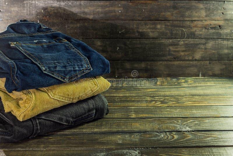 Stapel von Hosen von den verschiedenen Farben braun, blau und schwarz auf einem hölzernen Regal lizenzfreie stockbilder
