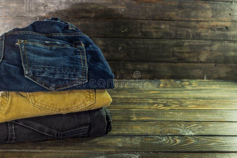 Stapel von Hosen von den verschiedenen Farben braun, blau und schwarz auf einem hölzernen Regal stockbild