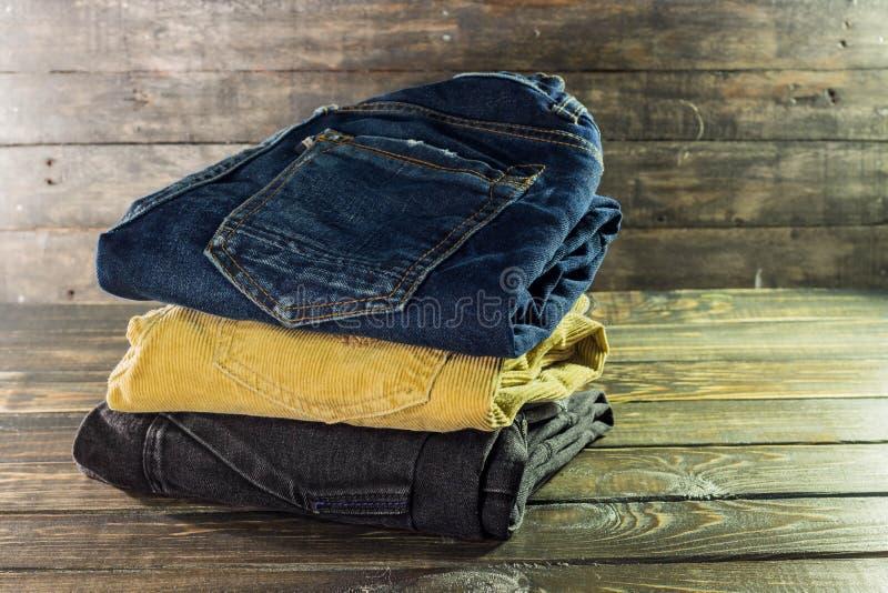 Stapel von Hosen von den verschiedenen Farben braun, blau und schwarz auf einem hölzernen Regal stockfotos