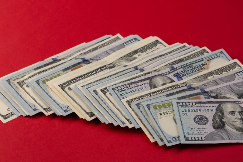 Stapel von hundert Dollarscheinen neu und von altem Design auf rotem Hintergrund lizenzfreie stockfotos