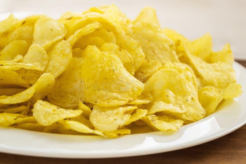 Stapel von knusperigen Kartoffelchips in einer weißen Platte auf einer Tabelle Schnellimbiß und geschmackvolles Imbisskonzept stockfoto