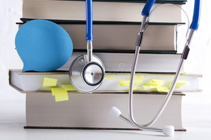 Stapel von medizinischen Büchern, von professionellem medizinischem Werkzeug und von Papier für Anmerkungen Konzept von Mittelaus lizenzfreie stockfotografie