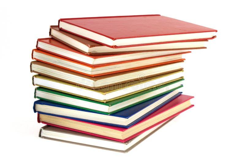 Stapel von mehrfarbigen Büchern auf einem weißen Hintergrund stockfoto