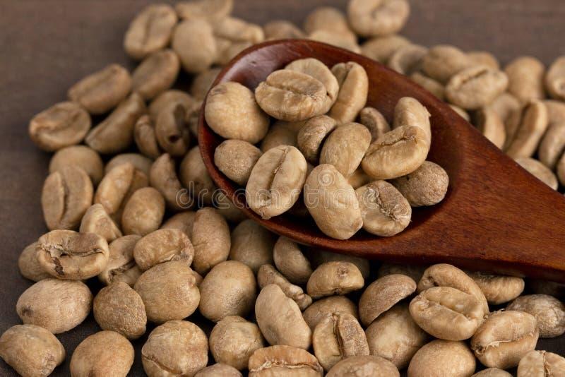 Stapel von rohen Rohkaffee-Bohnen mit einem hölzernen Löffel stockbilder