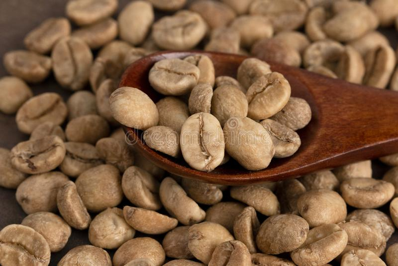 Stapel von rohen Rohkaffee-Bohnen mit einem hölzernen Löffel stockfotografie