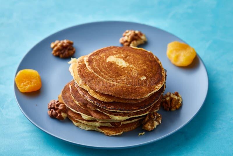 Stapel von selbst gemachten Pfannkuchen mit Honig und Walnüssen auf blauem Hintergrund, selektiver Fokus stockfotografie