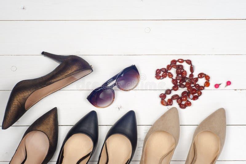 Stapel von verschiedenen weiblichen Schuhen, Gläser, Perlen lizenzfreie stockfotos
