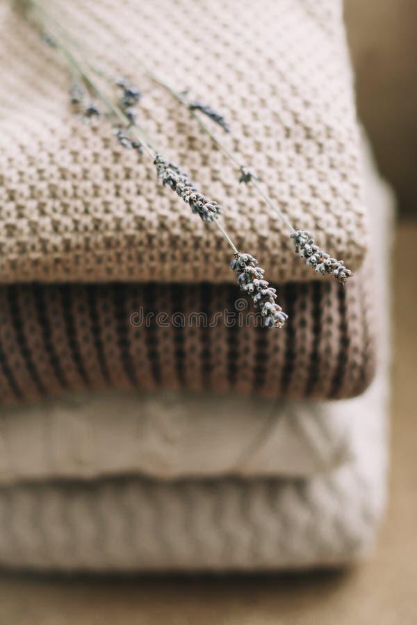 Stapel von woolen Plaids auf einem hellen Hintergrund Stapel gestrickte Kleidungsstrickjacken, Schals, Pullover lizenzfreies stockfoto