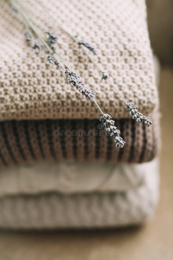 Stapel von woolen Plaids auf einem hellen Hintergrund Stapel gestrickte Kleidungsstrickjacken, Schals, Pullover stockfoto