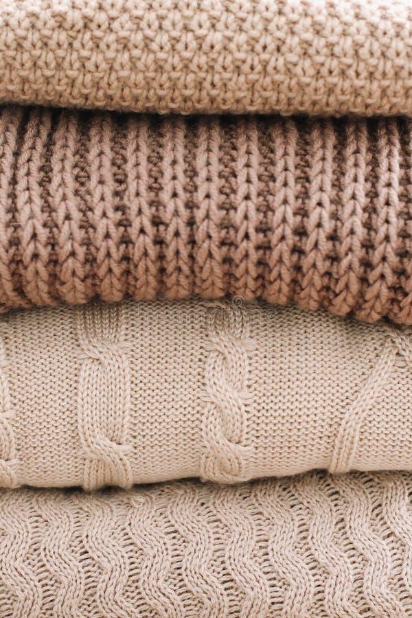 Stapel von woolen Plaids auf einem hellen Hintergrund Stapel gestrickte Kleidungsstrickjacken, Schals, Pullover stockbilder