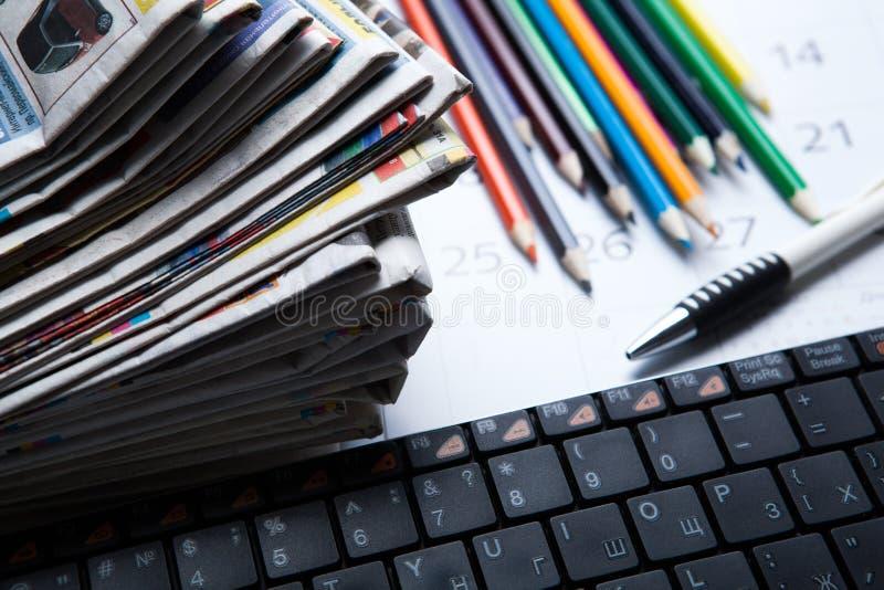 Stapel von Zeitungen und von Tastaturnahaufnahme stockfoto