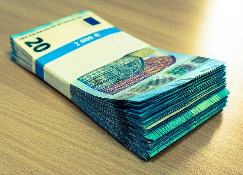 Stapel von zwanzig Eurorechnungen auf einem Kiefernschreibtisch stockbild