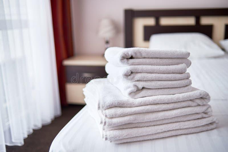 Stapel weiße saubere Badetücher auf Bettlaken im modernen Hotelschlafzimmerinnenraum, Kopienraum stockfoto