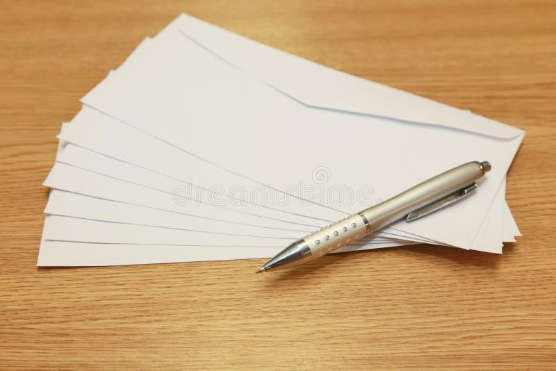 Stapel witte enveloppen op een lijst stock afbeelding