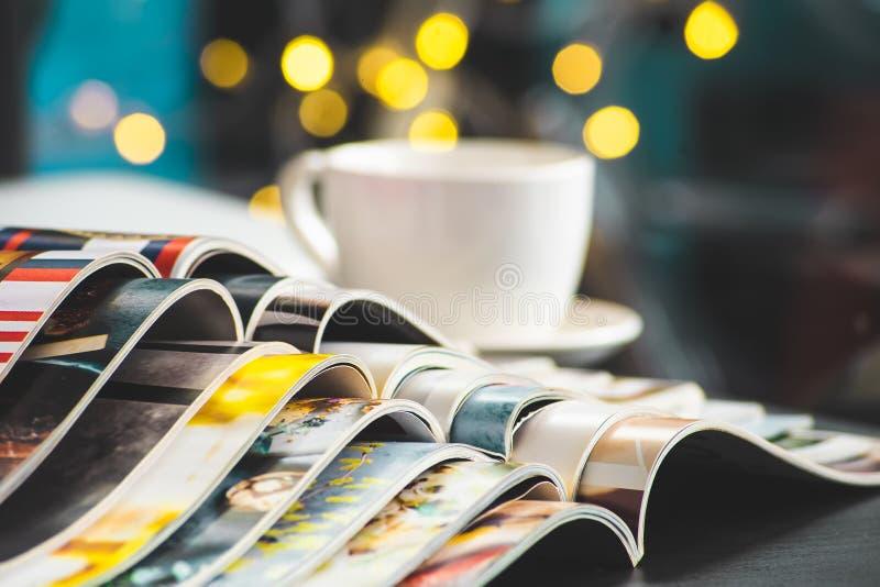 Stapel-Zeitschriftenplatz oder alte Bücher auf schwarzem Schreibtisch mit Kaffeetassehintergrund Selektiver Fokus lizenzfreies stockbild