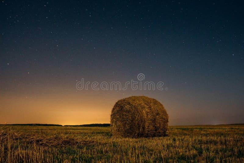 Stapeln Sie trockenes Heu unter dem nächtlichen Himmel mit Sternen stockfotografie