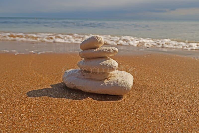 Stapelo F stenen op een zandig strand royalty-vrije stock fotografie