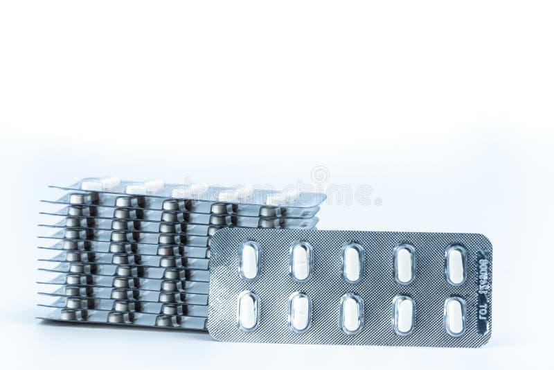 Stapels antidieallergiepillen in blaarpakken op witte achtergrond worden geïsoleerd Farmaceutische markt Cetirizine: antihistamin stock foto