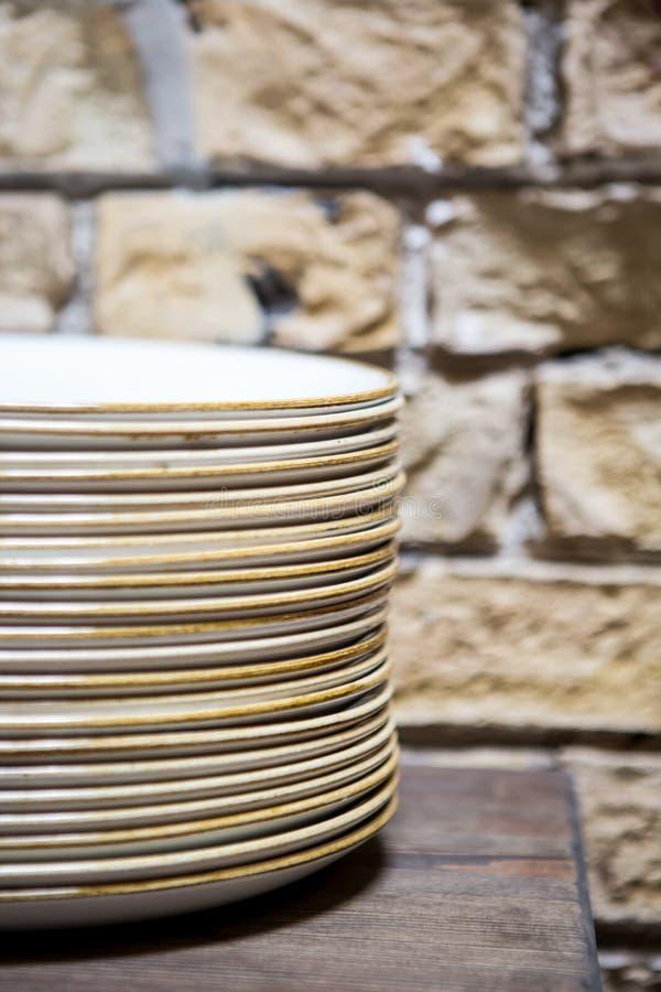 Stapels schoongemaakte witte platen voor cateringsbuffet in restaurantruimte Samen gestapelde groepsplaten stock afbeelding