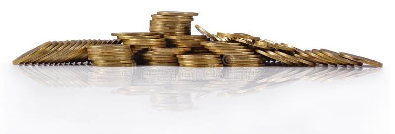 Stapels van gouden muntstukken op een wit royalty-vrije stock afbeelding