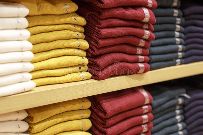 Stapels van multicolored kleren op de planken in opslag royalty-vrije stock afbeelding