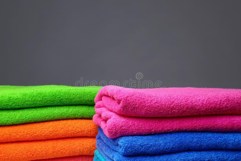 Stapels zachte kleurenhanddoeken op grijze achtergrond stock foto's