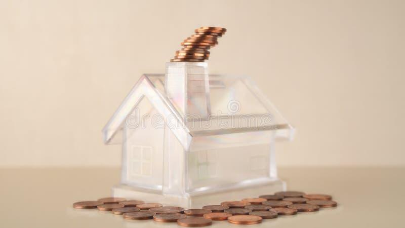 Stapelt het witte transparante huis van het spaarvarken met schoorsteen, muntstukken rook, financiële beheerszaken en investering royalty-vrije stock foto