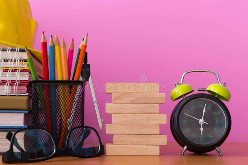 Stapla träkvarter med blyertspennor, avdelare, exponeringsglas, konstruktionshjälmen, klockan och bunten av boken på trätabellen royaltyfri foto
