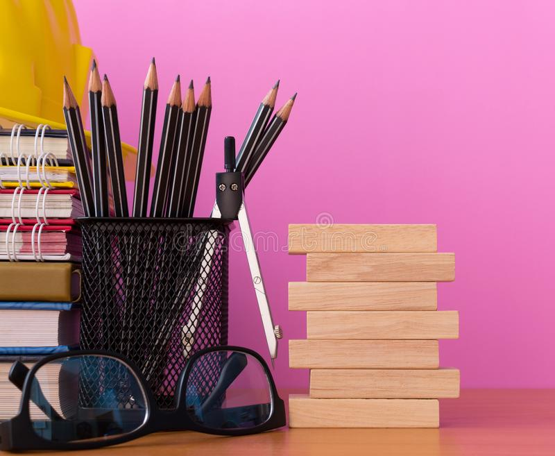 Stapla träkvarter med blyertspennor, avdelare, exponeringsglas, konstruktionshjälmen och bunten av boken på trätabellen royaltyfria bilder