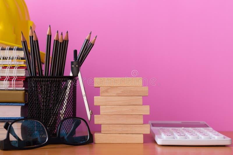 Stapla träkvarter med blyertspennor, avdelare, exponeringsglas, konstruktionshjälmen, räknemaskinen och bunten av boken på trätab arkivbild