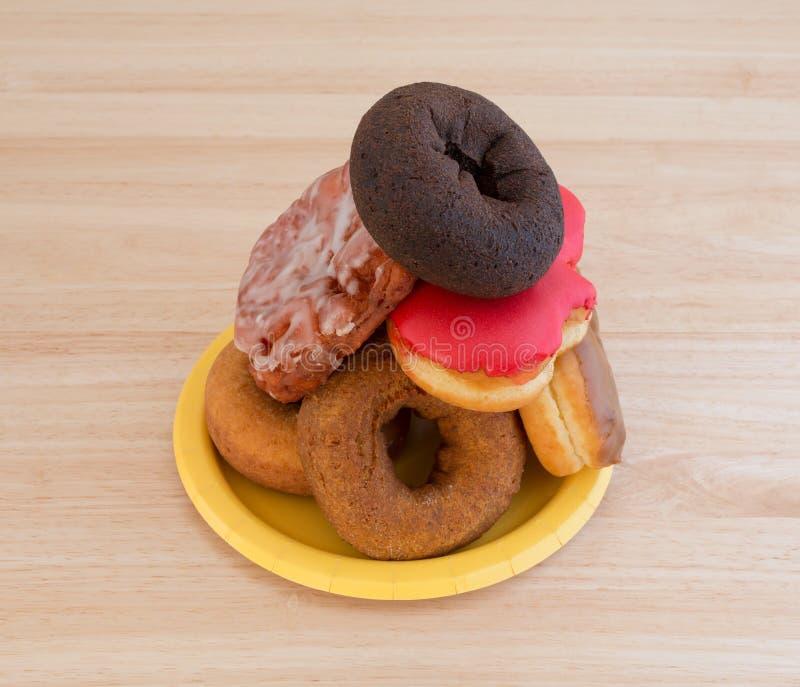 Staplad donuts och struva på en gul plattatabellöverkant royaltyfria bilder