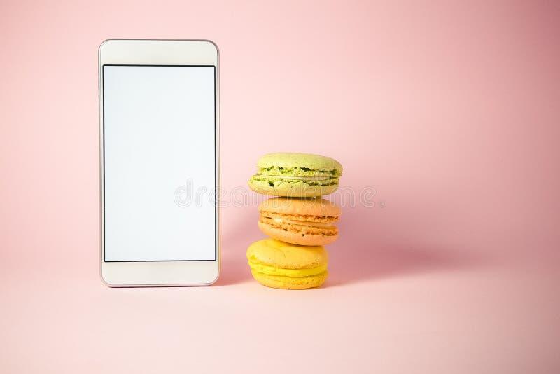 Staplad färgrik macarons och smartphone med den tomma skärmen royaltyfri bild