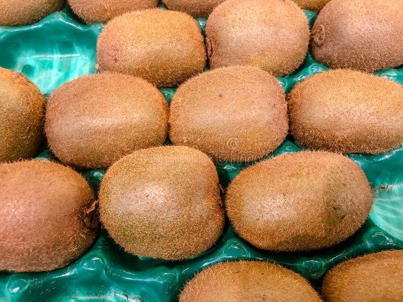 Staplad grupp av kiwifruits, kiwi eller kinesiskt krusbär, som är ett ätligt bär från Actinidiasläkte Detaljerad hårig textur av royaltyfri foto